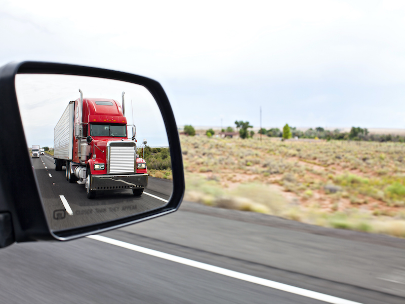 Side mirror showing an approaching semi-truck